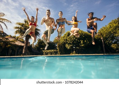 Group of crazy young people jumping into a swimming pool. Friends having fun at a holiday resort.