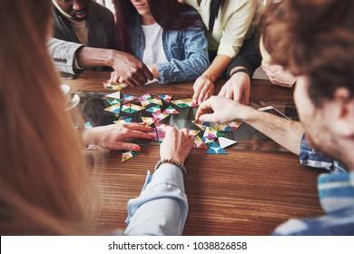 Gruppe kreativer Freunde, die am Holztisch sitzen. Leute, die Spaß beim Brettspielen haben.