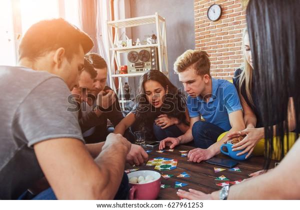 Группа творческих друзей сидит за деревянным столом. Люди, получающие удовольствие во время игры в настольные игры.