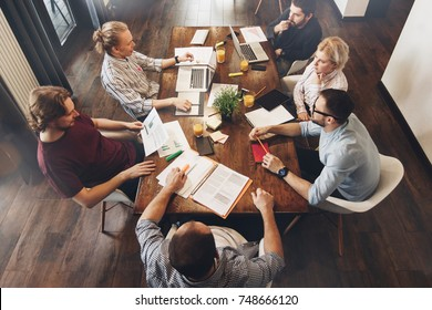 Group of creative managers sits around table. Working process. Teamwork on new project. Coworkers sitting at wooden table and working together on laptops and paper documents