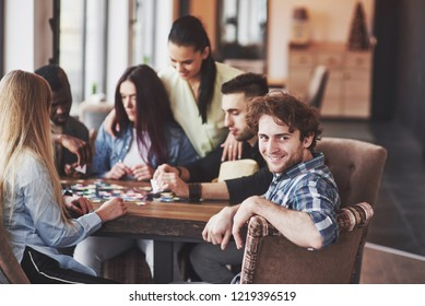 Group of creative multietnic friends sitting at wooden table. People having fun while playing board game.