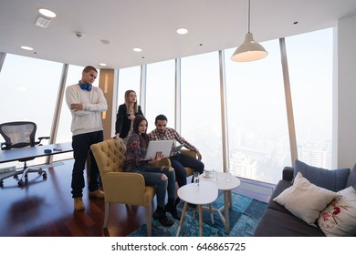Group of creative people having a meeting with a laptop in a modern office. Business people having relaxed conversation over new project.