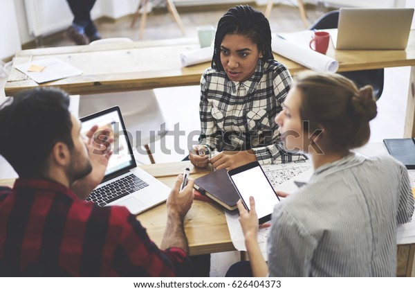 Group of creative talented coworkers communicating together about work questions while sitting ash the table in modern office space. Young university students preparing project while studying together