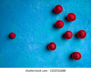 A group of crimson chocolate truffles in red wrappers opposes one raspberry truffle without a wrapper. Standoff concept.