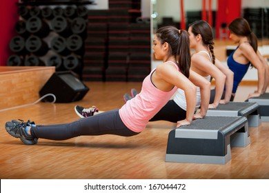 Group of cute female Hispanic friends exercising together during a gym class