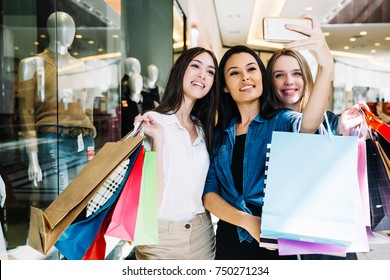 Group of cute girl friends doing some shopping at a mall and taking a selfie with a smartphone