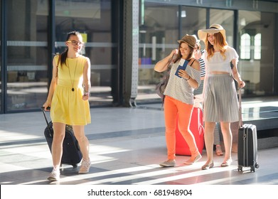 Group of cute girls at the railway station. Tourists with tickets and luggage are hurrying to their train. Time of summer holidays.
