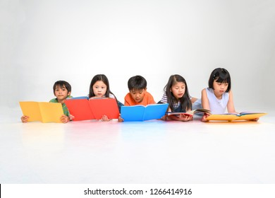 a group of Cute little asian boy and girl reading book while sitting or lying over white background