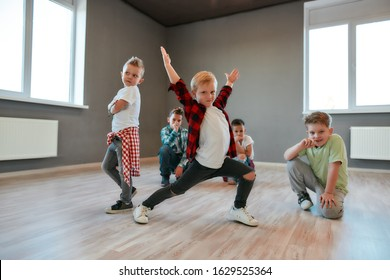 Group of cute little boys in fashionable clothes dancing and posing in the studio. Choreography class. Kids and sport. Full length