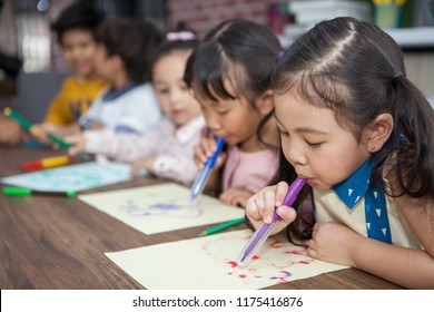 group of Cute little girl and boy student blowing color pen painting  together with nursery teacher in classroom school . Happy children in a kindergarten . kid artist multiethnic