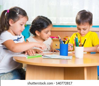 Group of cute little preschol kids drawing with colorful pencils
