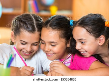 Group of cute schoolchildren drawing and having fun in classroom