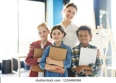 Group of cute schoolkids with notepads and their teacher looking at camera in classroom after lesson of painting