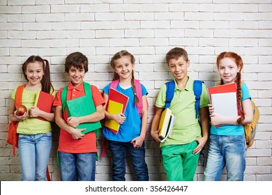 Group of cute schoolkids standing by wall and looking at camera