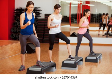 Group of cute women working out and doing some step aerobics