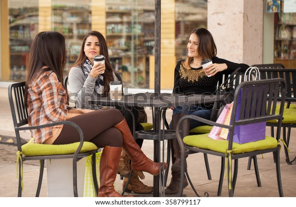 Group of cute young women sitting in a restaurant and drinking coffee after a day of shopping