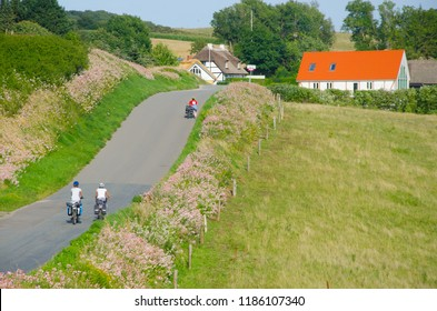 Group of  cycle tourist on the scenic countryside road in Denmark - island Mon (near Busene).