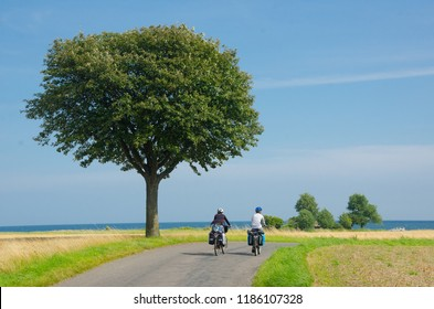 Group of cycle tourists on the scenic countryside road in Denmark - island Mon.