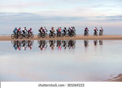 a group of cyclist race over the beach during a mountain bike contest. The water in the front shows a nice reflection.