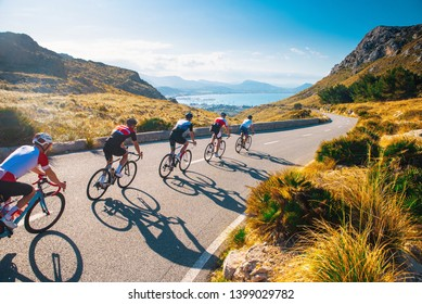 Group of cyclist ride together on road bicycles in beautiful nature. Sunset light, sea in background.