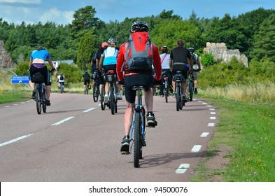 A group of cyclists going on the road in the countryside
