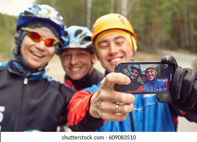 group of cyclists in helmets taking selfie photo. team outdoors. mountain bike