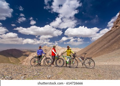 Group of cyclists with a large backpack for bicycling, standing on a mountain dirt road, winding road in the dry desert valley. Sunny day, high mountains. Tien Shan, Kyrgyzstan, Asia