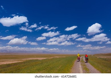 group of cyclists with a large backpack for bicycling, ride along a mountain, dirt road, winding road in the dry, desert, valley. Sunny day, high mountains. Tien Shan, Kyrgyzstan, Asia