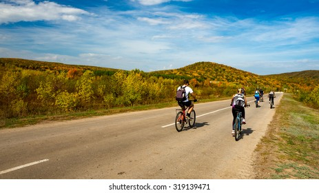 Group of cyclists on road stretches into the distance on the background of bright autumn trees on a hill. Zhiguli, Russia