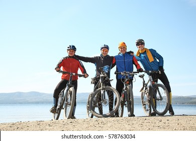 group of cyclists on a shore of a mountain lake. team outdoors. mountain bike