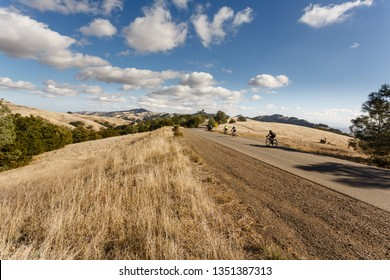 Group of Cyclists powers up long hill on bicycles in Mt Diablo Park on sunny day