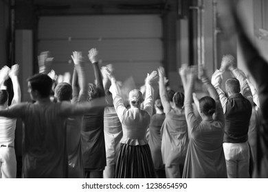 A group of dancers in costumes stand with their hands up