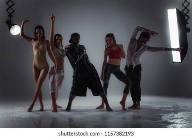 Group of dancers dancing under the rain