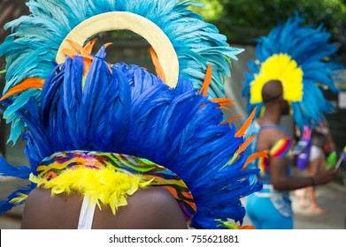 Group of dancers wearing colorful feathers costumes gathered for a carnival parade