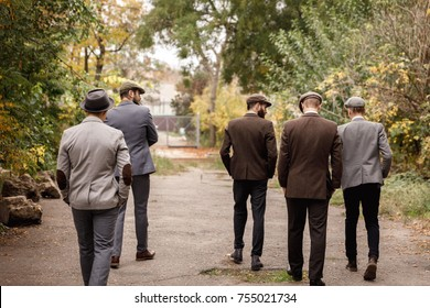 Group of dangerous retro gangsters in the park, view from the back.
