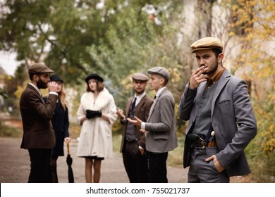 Group of dangerous retro gangsters in the park, smoking.