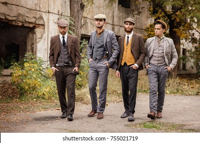 A group of dangerous retro gangsters are walking in the park.
