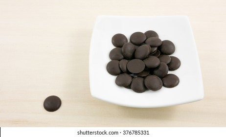 The group of dark chocolate buttons and small white square disk on light brown wooden board.