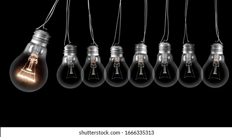 Group of dark and shining light bulbs in a row isolated on black background. Concept of Idea, Innovation, Success and Creativity.