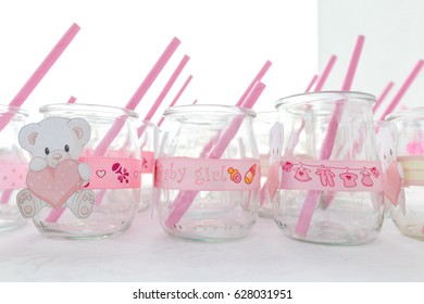 Group of decorative empty jars with straws in them, read to serve drinks at a girl baby shower