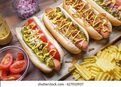 Group of Delicious Gourmet Grilled Hot Dogs With Mustard, Pickles, Onion and Chips