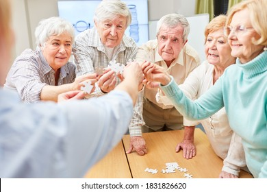 Group of demented seniors trains their memory while playing puzzles in a nursing home