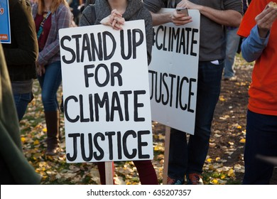 Group of demonstrators hold a sign demanding climate justice