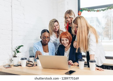 Group of designers working on a project as a team, diverse women gathered together near laptop of red-haired female colleague.