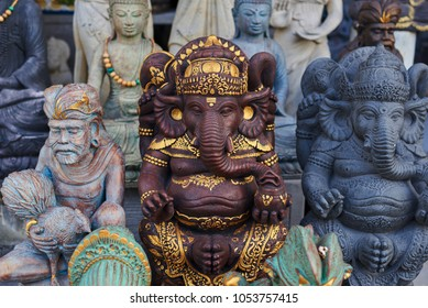 Group of different  Balinese wooden statues displayed in art and craft tourist market. Indonesian handicrafts. Souvenir from Bali. Traditional wood carving. Ð¡ounter with balinese souvenirs.