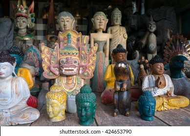 Group of different colored Balinese wooden statues displayed in art and craft tourist market in Ubud. Bali Island. Indonesia
