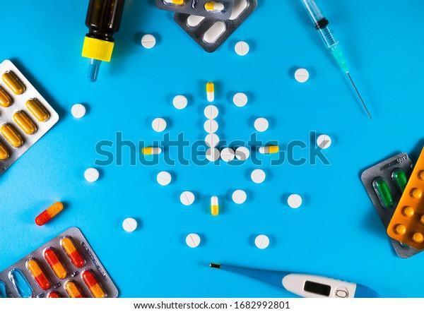 Grupo de diferentes pastillas dispuestas en forma de reloj sobre fondo azul. Tiempo en farmacia. Tiempo en medicina.