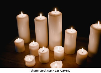 A group of different sized candles stands on a simple wooden table in the darkness.