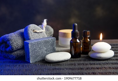 Group of different spa essentials, beard oil, gray soap, natural loofah sponge, candle, aroma oil on wooden and black background. Father, brother or husband gift idea concept. Blue color back light.