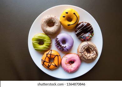 Group of different taste and multiple coloured icing donuts on a white plate. Many mini donuts. Colour glaze. isolated on dark brown leather background